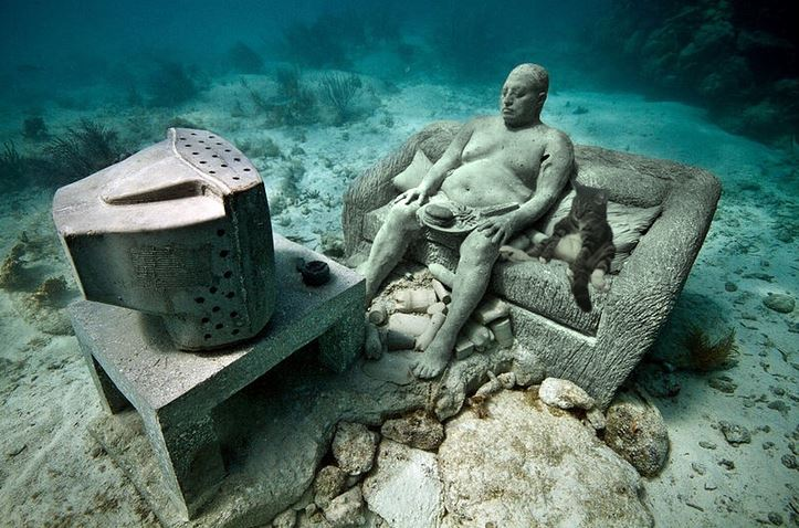 underwater statues of man and cat