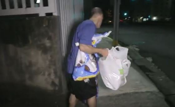 glen carrying his daily supplies to the cats at night