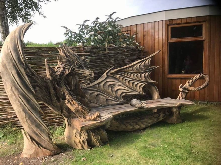 cat sits on dragon bench